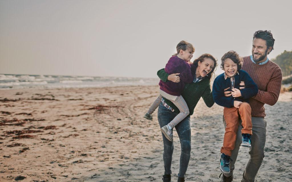 Gelukkige familie van vader en moeder en twee kinderen op het strand.