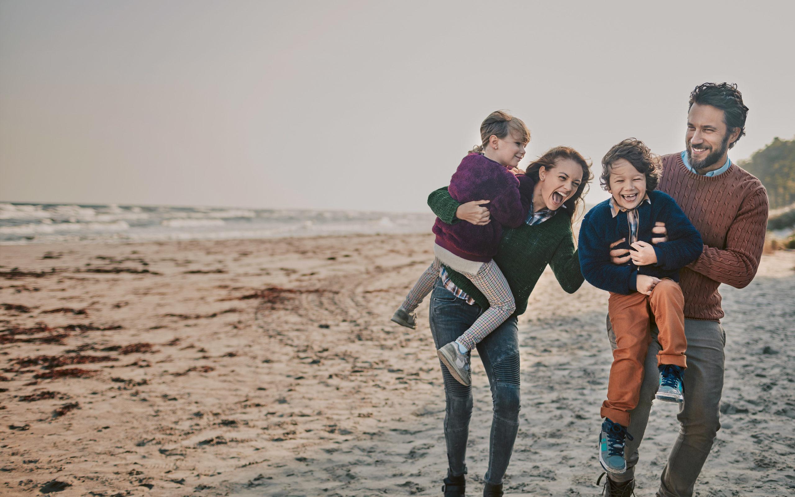Un couple avec deux enfants rient lors d'une ballade sur la plage