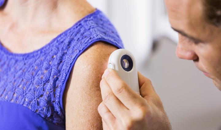 Dermatoloog die de huid van de bovenarm van een patiënt onderzoekt met een speciaal apparaat.