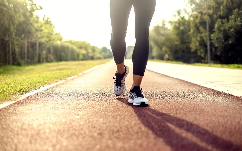 Vrouwenbenen met sportschoenen die aan het lopen zijn.
