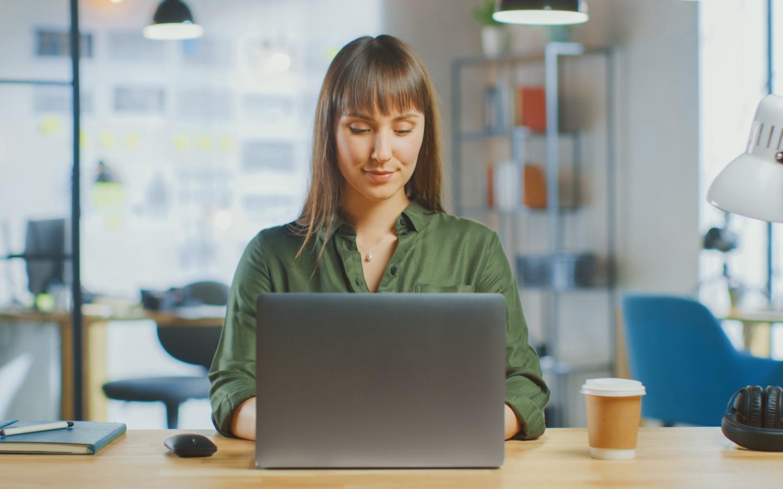 Jonge vrouw met groene blouse achter laptop in werkomgeving.