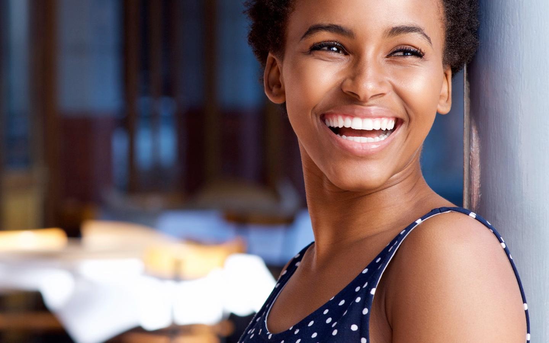 Jonge vrouw met glimlach die leunt tegen een muur.