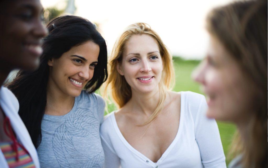 Groep vrouwen aan het praten en lachen.