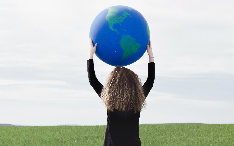 Foto van een meisje op de rug gezien met zwart t-shirt en gestrekte armen. Ze houdt een grote globe boven haar hoofd.