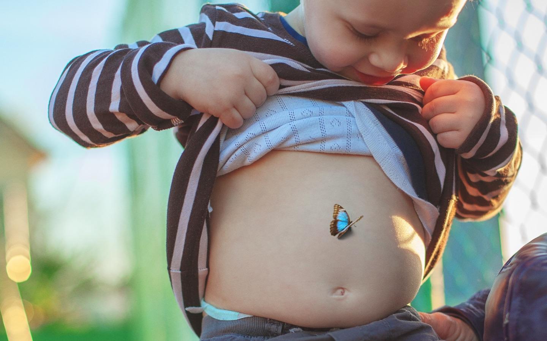 Een kleine jongen doet zijn shirt omhoog en toont zijn buik, met op die buik het beeld van een vlinder.