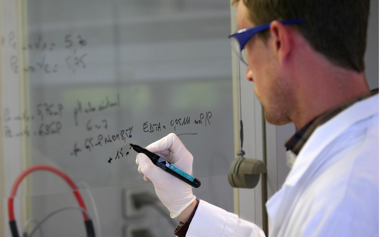 Mannelijke wetenschapper met witte jas, beschermbril en handschoenen schrijft met zwarte marker formules op een whiteboard.